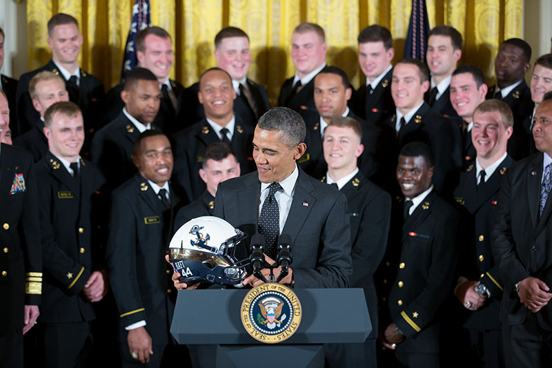 President Barack Obama examines the helmet given to him by the United States Naval Academy, who won the Commander-in-Chief Trophy, April 12, 2013