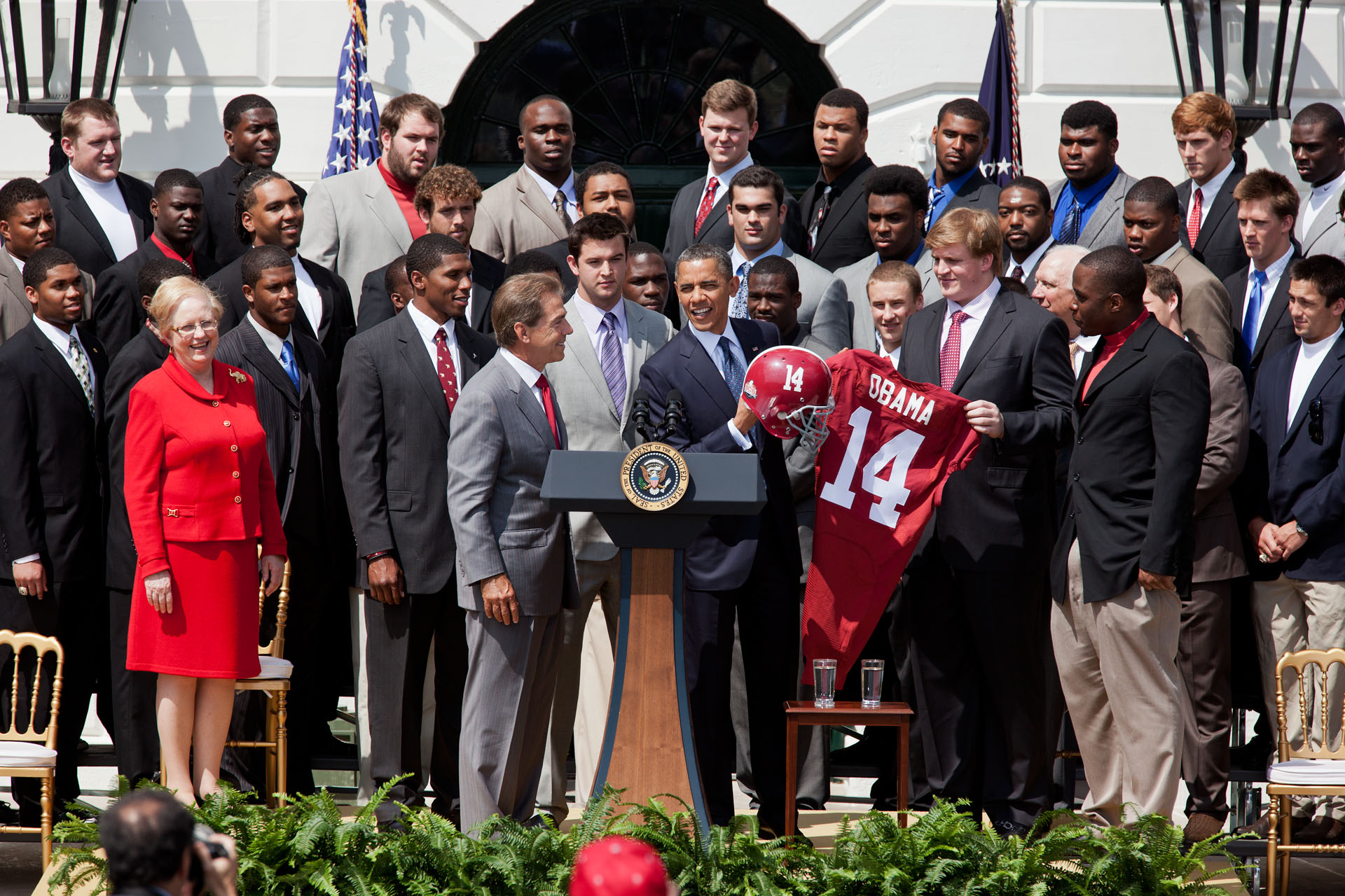 University of Alabama present President Obama with a jersey and helmet