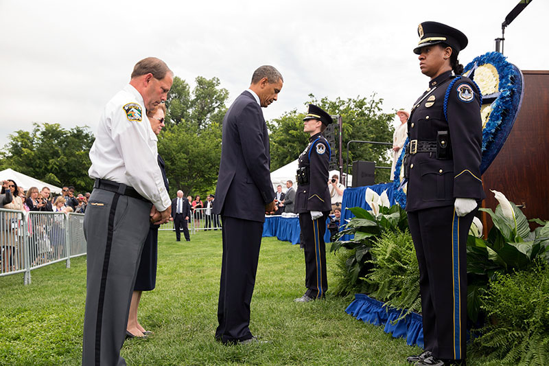 White House caption from 2013 ceremony: President Barack Obama bows his head after placing a flower in a wreath during the National Peace Officers Memorial Service, an annual ceremony honoring law enforcement who were killed in the line of duty in the previous year, at the U.S. Capitol in Washington, D.C. May 15, 2013. Chuck Canterbury, National President, Fraternal Order of Police and Linda Hennie, President, FOP Auxiliary stand with the President. (Official White House Photo by Pete Souza)