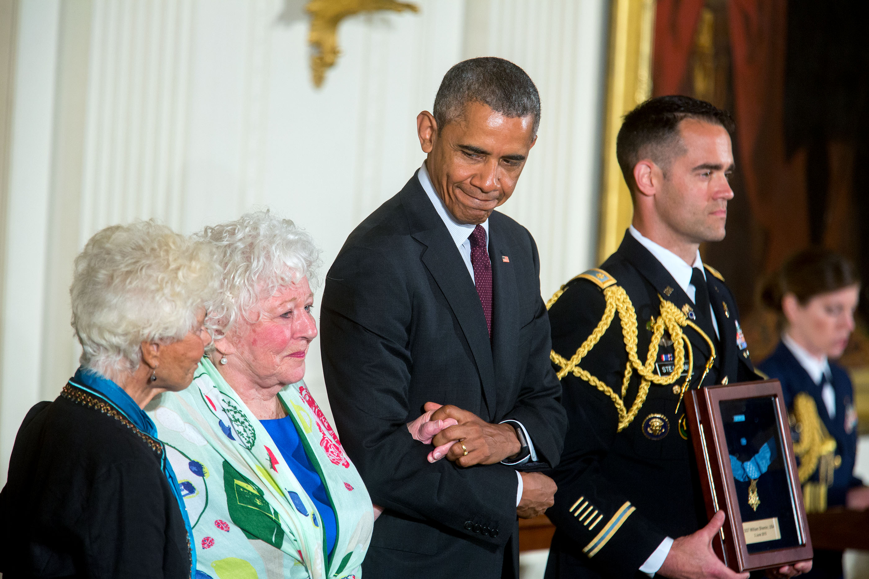 President Barack Obama stands with Ina Judith Bass (left) and Elise Shemin-Roth as the citation is read awarding the Medal of Honor posthumously to their father, Army Sergeant William Shemin, for conspicuous gallantry during World War I, at a ceremony in