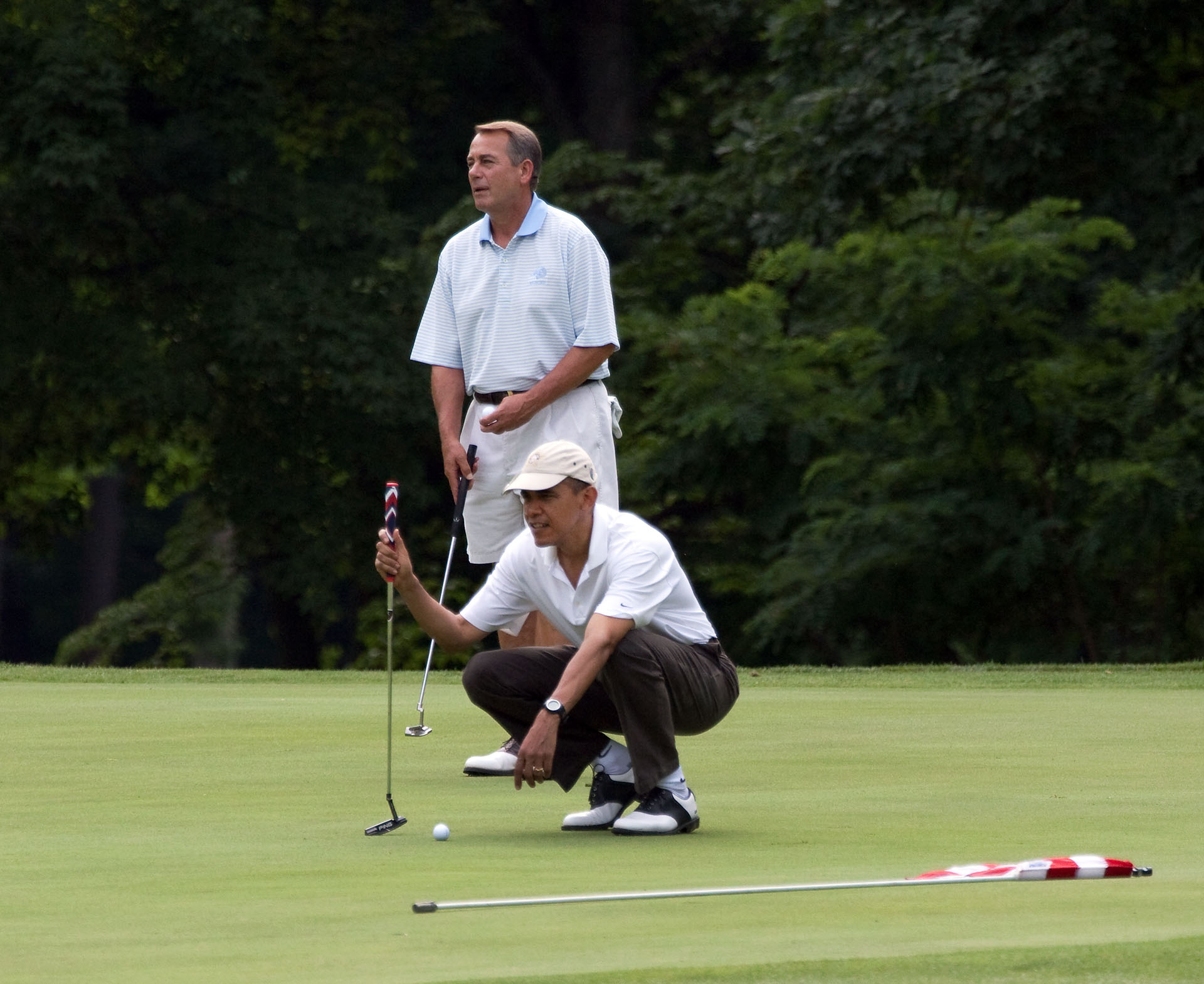 President Barack Obama lines up his putt as he plays a round of golf with House Speaker John Boehner