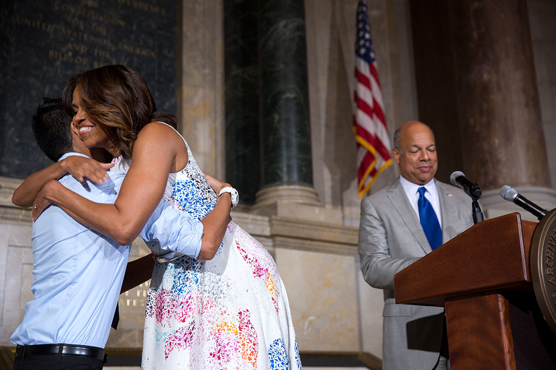 First Lady Michelle Obama hugs newly naturalized citizen Juan Cua Monroy