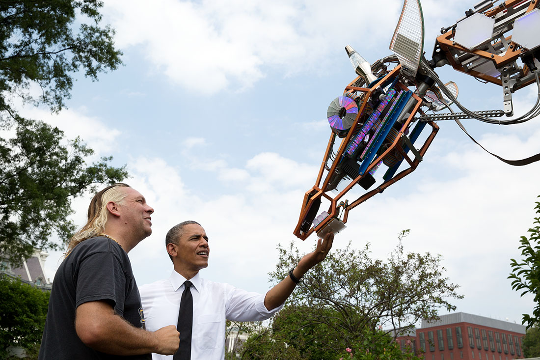 President Barack Obama looks at Lindsay Lawlor's robotic giraffe on the South Lawn of the White House