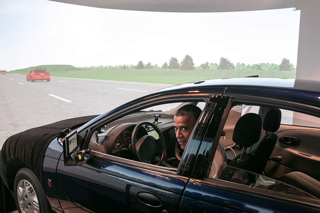 President Barack Obama prepares to drive a Saturn SL1 vehicle simulator