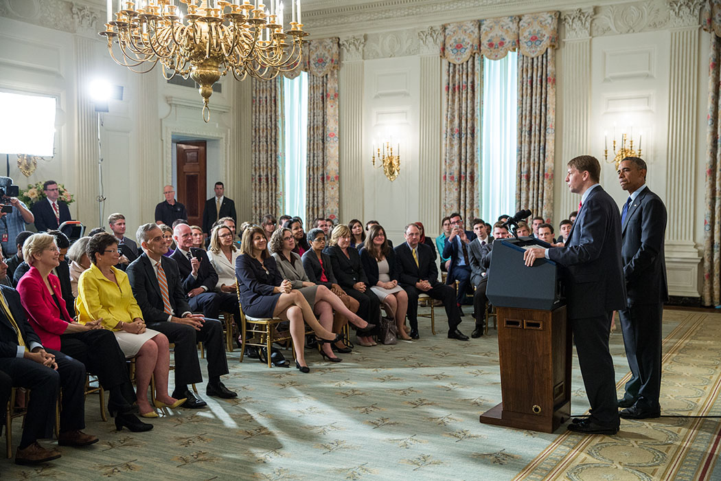 President Barack Obama listens to Richard Cordray deliver remarks following his confirmation as Director of the Consumer Financial Protection Bureau