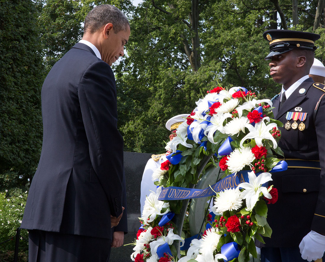 President Barack Obama bows his head during a  wreath laying ceremony to commemorate the 60th anniversary of the signing of the Armistice