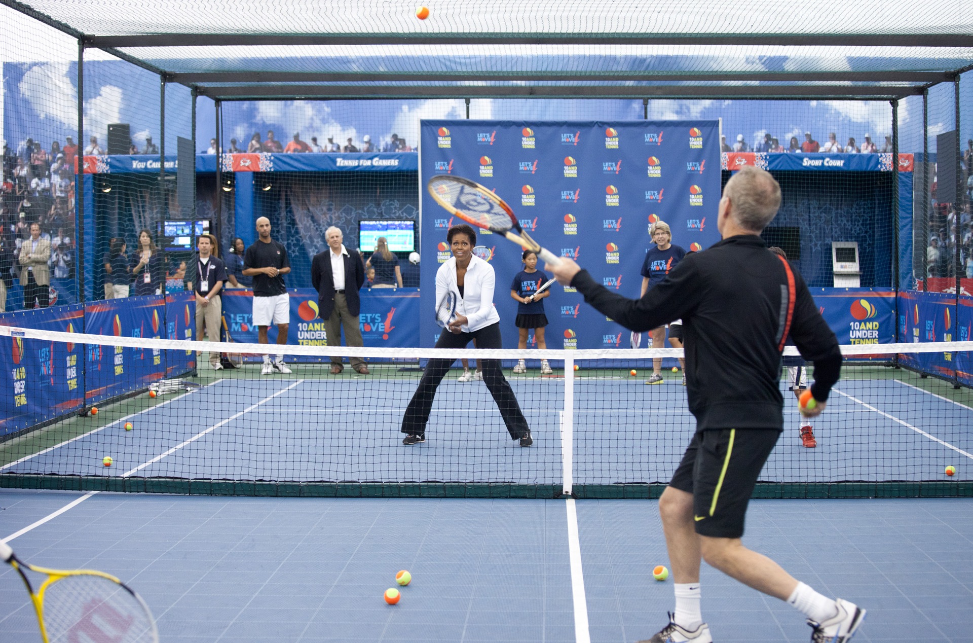 First Lady Michelle Obama hits tennis balls with John McEnroe