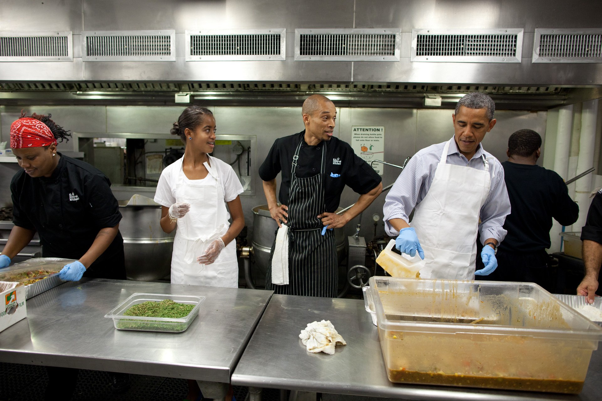 President Barack Obama and daughter Malia Obama participate in a service project at DC Kitchen