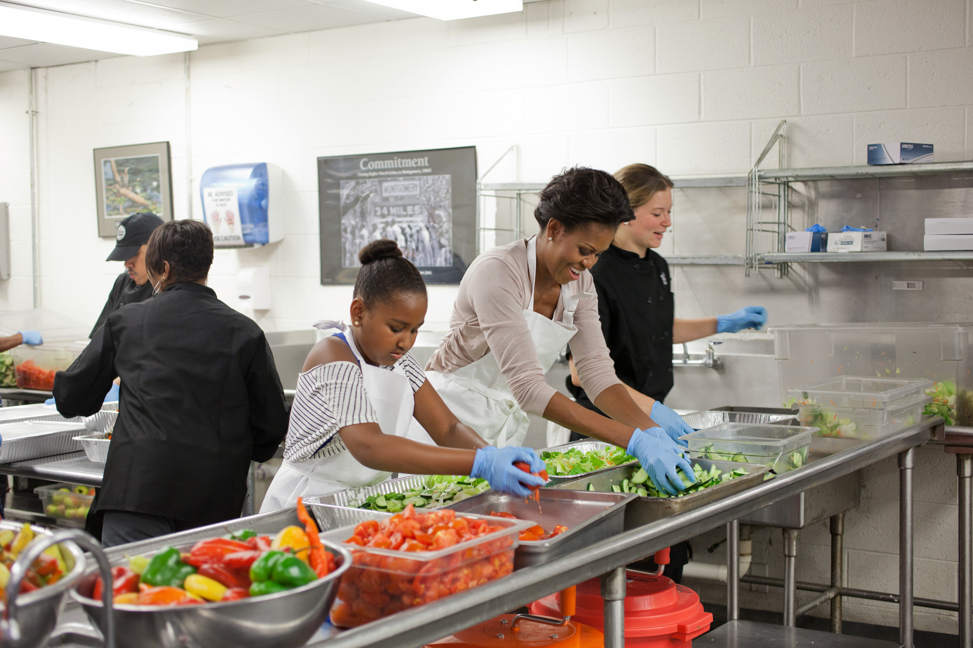 First Lady Michelle Obama and daughter Sasha Obama participate in a service event  at DC Central Kitchen