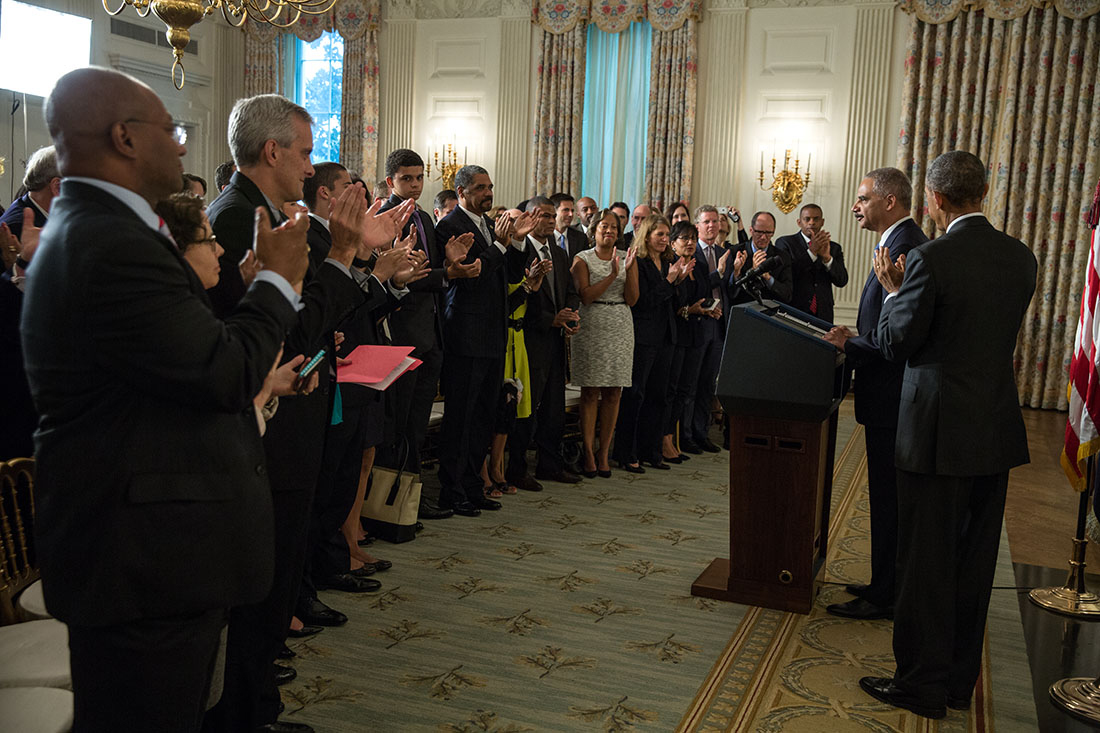 President Barack Obama joins a standing ovation for Attorney General Eric H. Holder Jr., during statements regarding Holder's resignation
