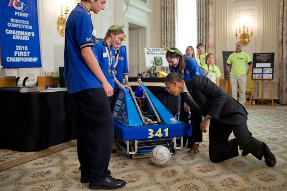 President Barack Obama gets down on his hands and knees as he looks at the inner workings of a robot that plays soccer