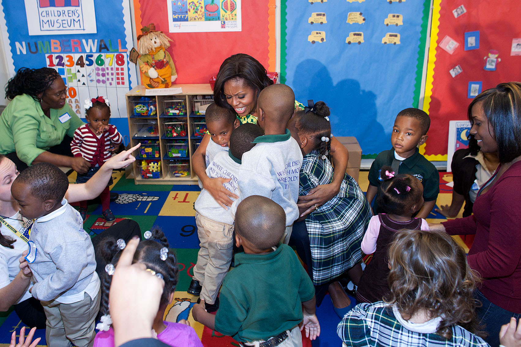 First Lady Michelle Obama shares a group hug with children at Royal Castle Child Development Center