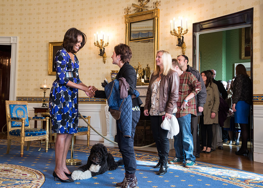First Lady Michelle Obama, with Obama family pet Bo, greets visitors in the Blue Room during a White House tour.