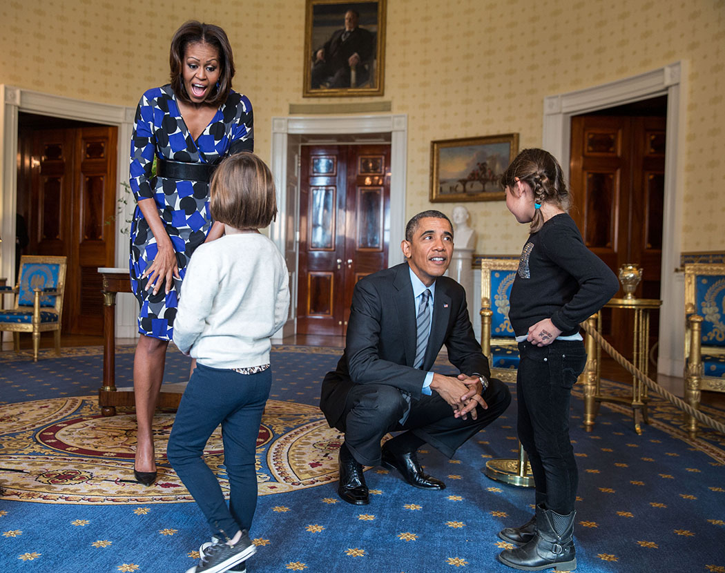 President Barack Obama and First Lady Michelle Obama greet visitors in the Blue Room during a White House tour.