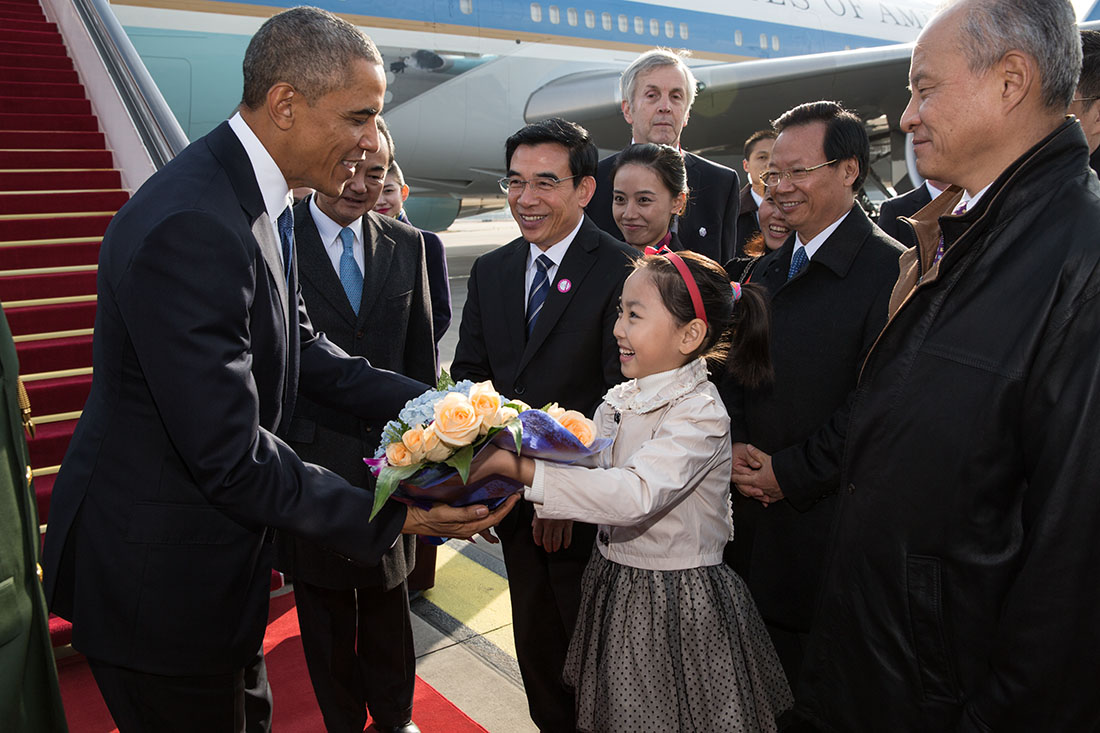 President Barack Obama is presented with a bouquet of flowers by a young Chinese girl upon arrival at Capital International Airport, Beijing