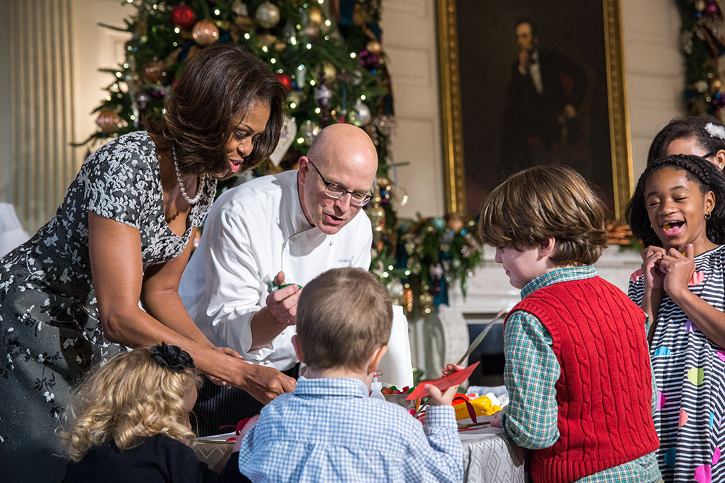 First Lady Michelle Obama and children of military families participate in a craft project in the State Dining Room during the White House holiday press preview, Dec. 4, 2013. Executive Pastry Chef Bill Yosses helps children decorate Springerle cookie orn