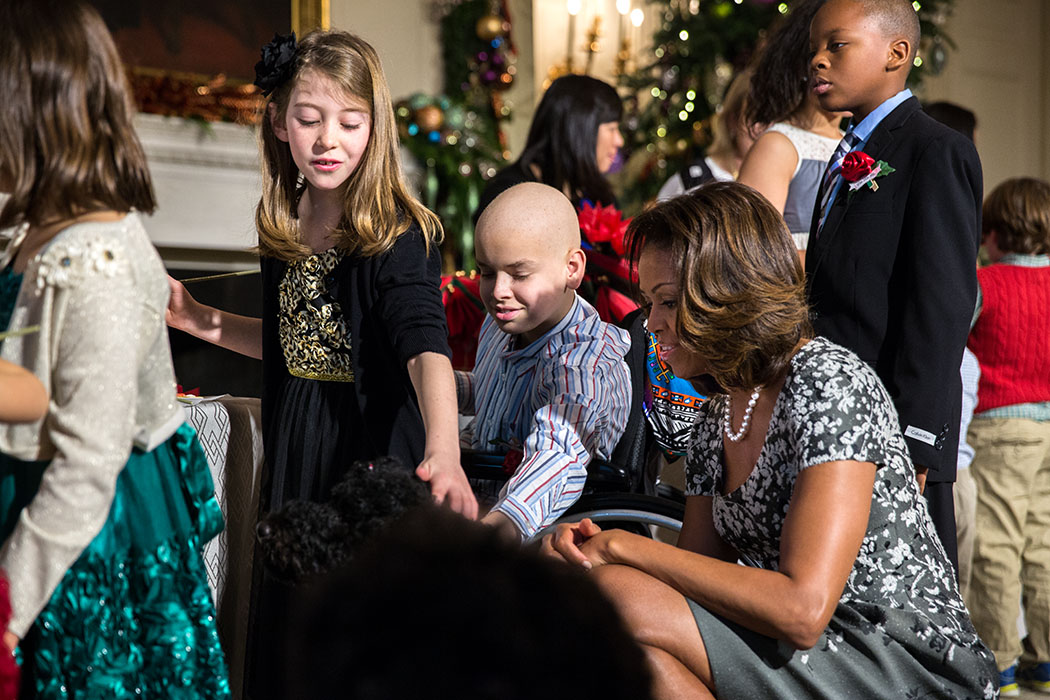 First Lady Michelle Obama and children of military families greet Obama family pet Sunny in the State Dining Room during the White House holiday press preview, Dec. 4, 2013.  (Official White House Photo by Amanda Lucidon)