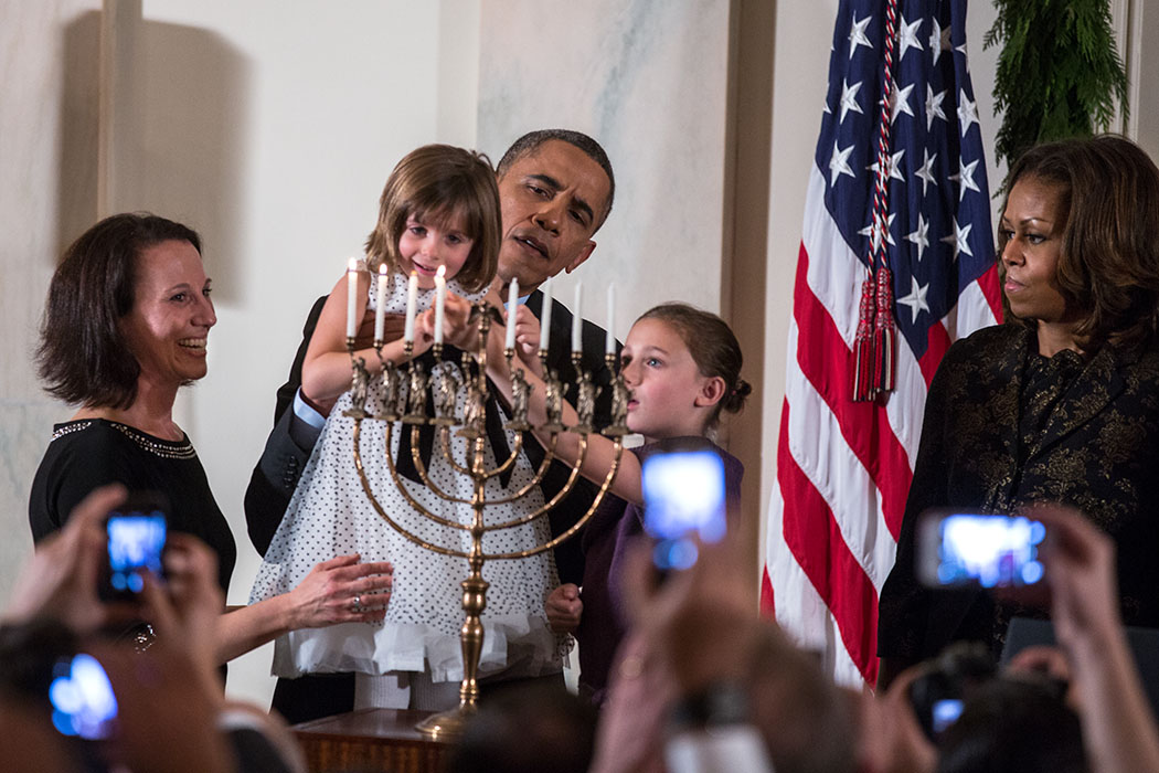 President Barack Obama holds up Kylie Schmitter as she and her sister Lainey Schmitter light the menorah during the Hanukkah reception