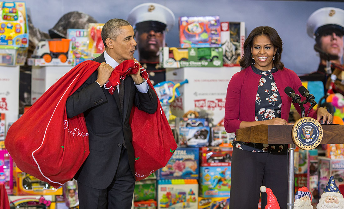 First Lady Michelle Obama, with President Obama carrying bags of toys, speaks at Toys for Tots event