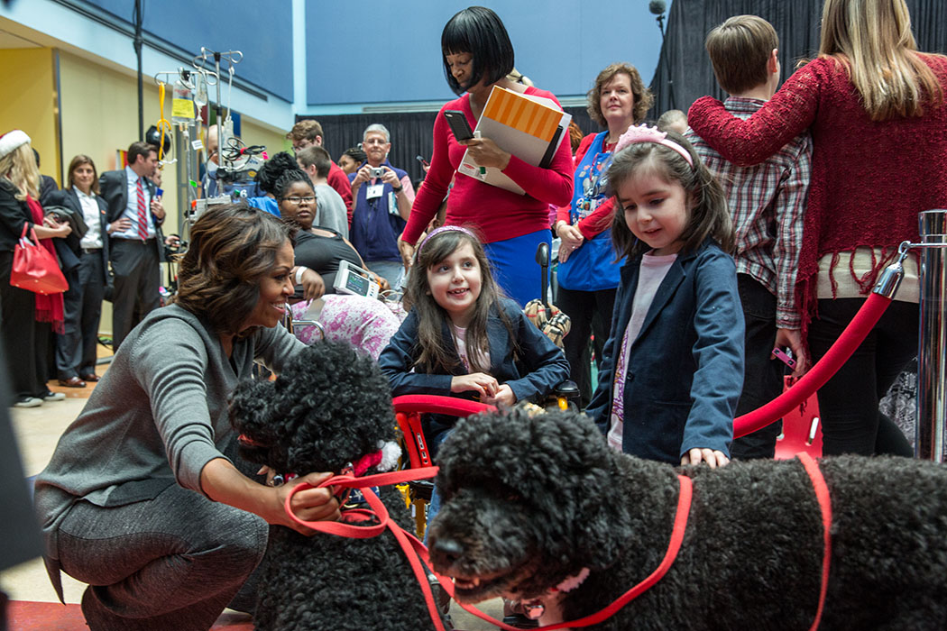 First Lady Michelle Obama, with Obama family pets, Bo and Sunny, greets children during a Christmas holiday program at the Children's National Medical Center in Washington, D.C., Dec. 16, 2013. (Official White House Photo by Amanda Lucidon)