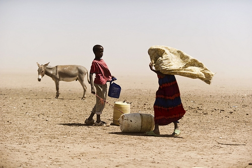 A boy and a woman struggle with dusty wind looking for water in Wajir, Kenya