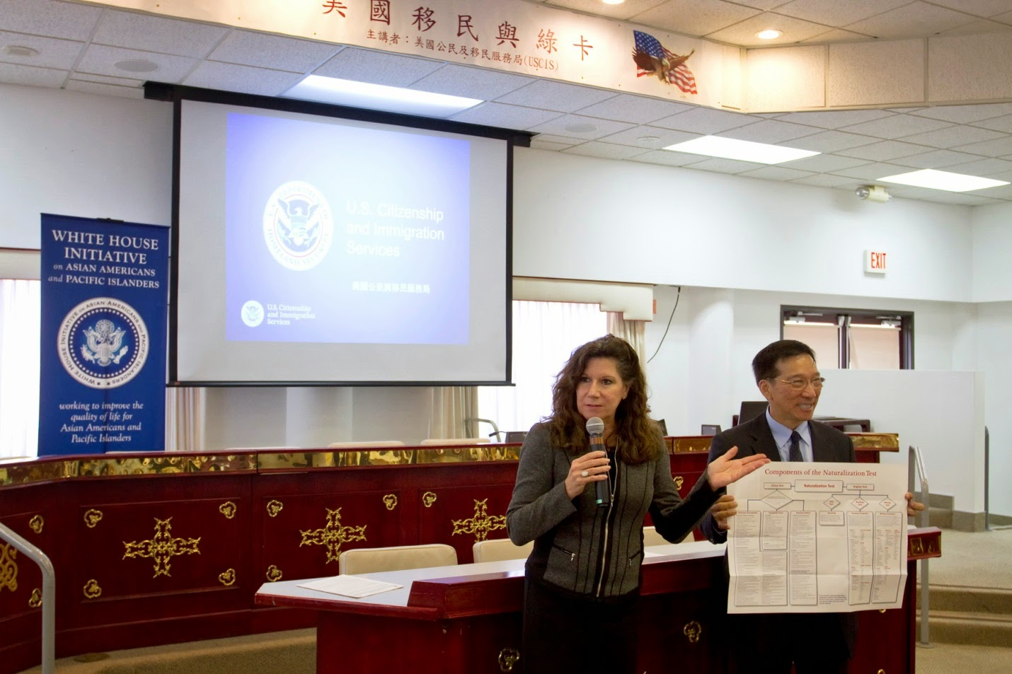 Susan M Curda (left) gives opening remarks and introduces the USCIS staff