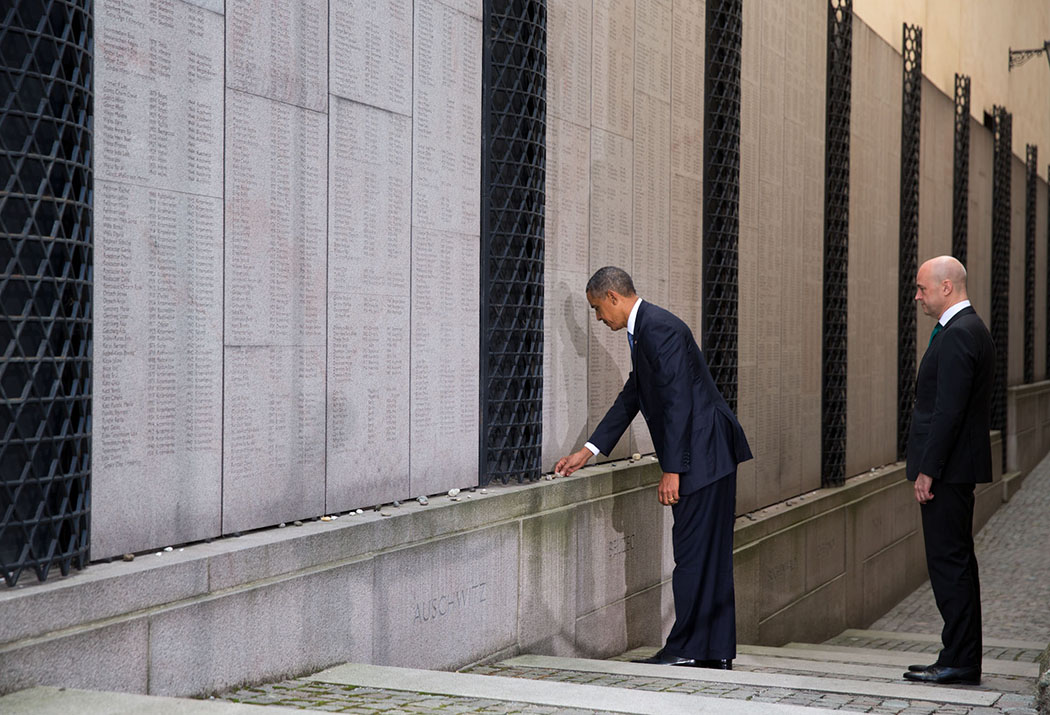 President Barack Obama and Swedish Prime Minister Fredrik Reinfeldt place stones and pause for a moment of reflection at the Holocaust Memorial