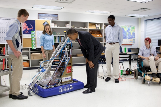 President Barack Obama examines a robot created in the school's prototyping and robotics senior research labs