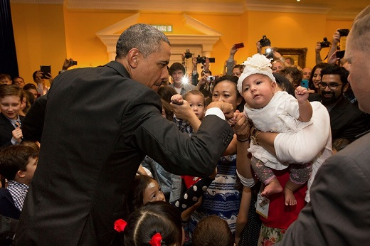 President Barack Obama gives a fist bump to a baby