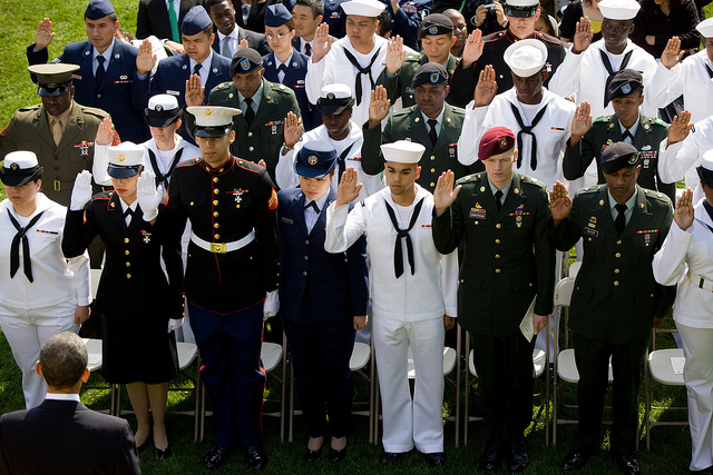 President Barack Obama looks on as active duty service members take an oath during a naturalization ceremony