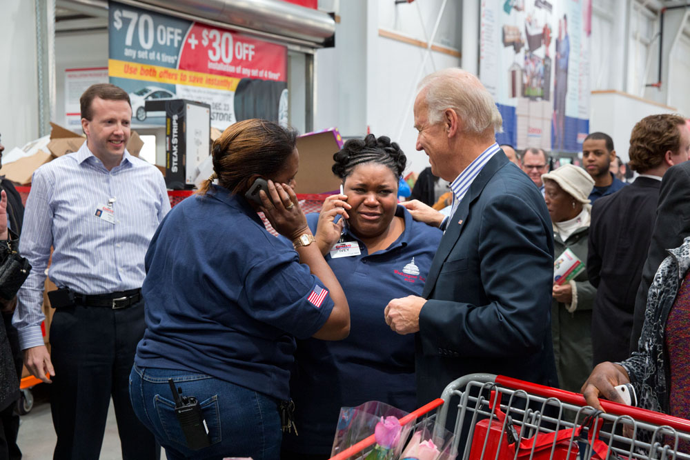 Vice President Joe Biden hugs employees at the newly opened Costco store