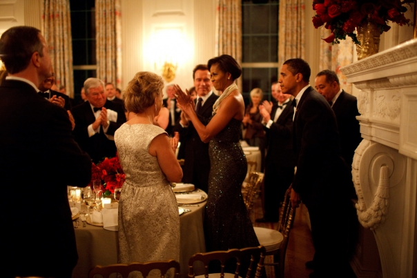 President Barack Obama pulls out the chair for First Lady Michelle Obama at the Governors Ball
