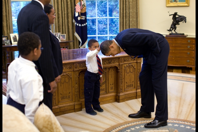 """A temporary White House staffer, Carlton Philadelphia, brought his family to the Oval Office for a farewell photo with President Obama. Carlton's son softly told the President he had just gotten a haircut like President Obama, and asked if he could feel the President's head to see if it felt the same as his."" May 8, 2009"