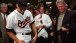 Baltimore Orioles player Cal Ripken autographs a baseball bat for President Clinton