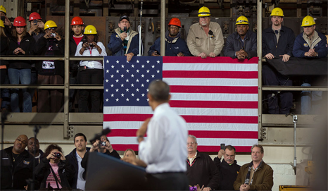 President Obama listens to questions from workers at an event