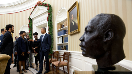 President Obama speaks with youth in the oval office with a bust of Martin Luther King Jr in the foreground