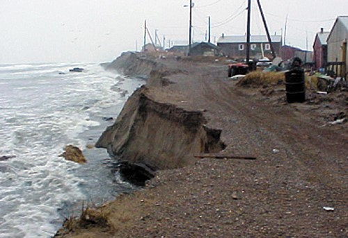 Waves break at the base of the bluff at Shishmaref, where severe coastal erosion  threatens this Iñupiat village on the Seward Peninsula in western Alaska. Photo: NOAA