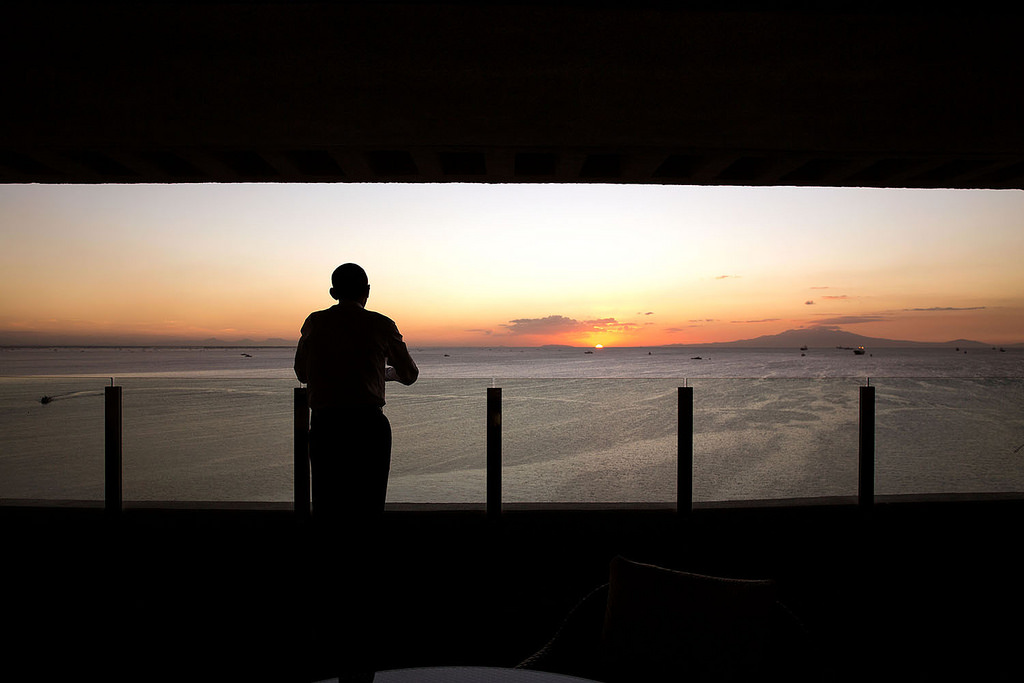 "The President watches the sun set over Manila Bay from his hotel balcony in Manila."" (Official White House Photo by Pete Souza)"