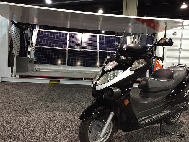 "Current Motor's ""Mini-Fleet-in-a-Box"" of electric scooters in a shipping container, which doubles as a solar-powered charging station, on display at the ARPA-E Innovation Summit."