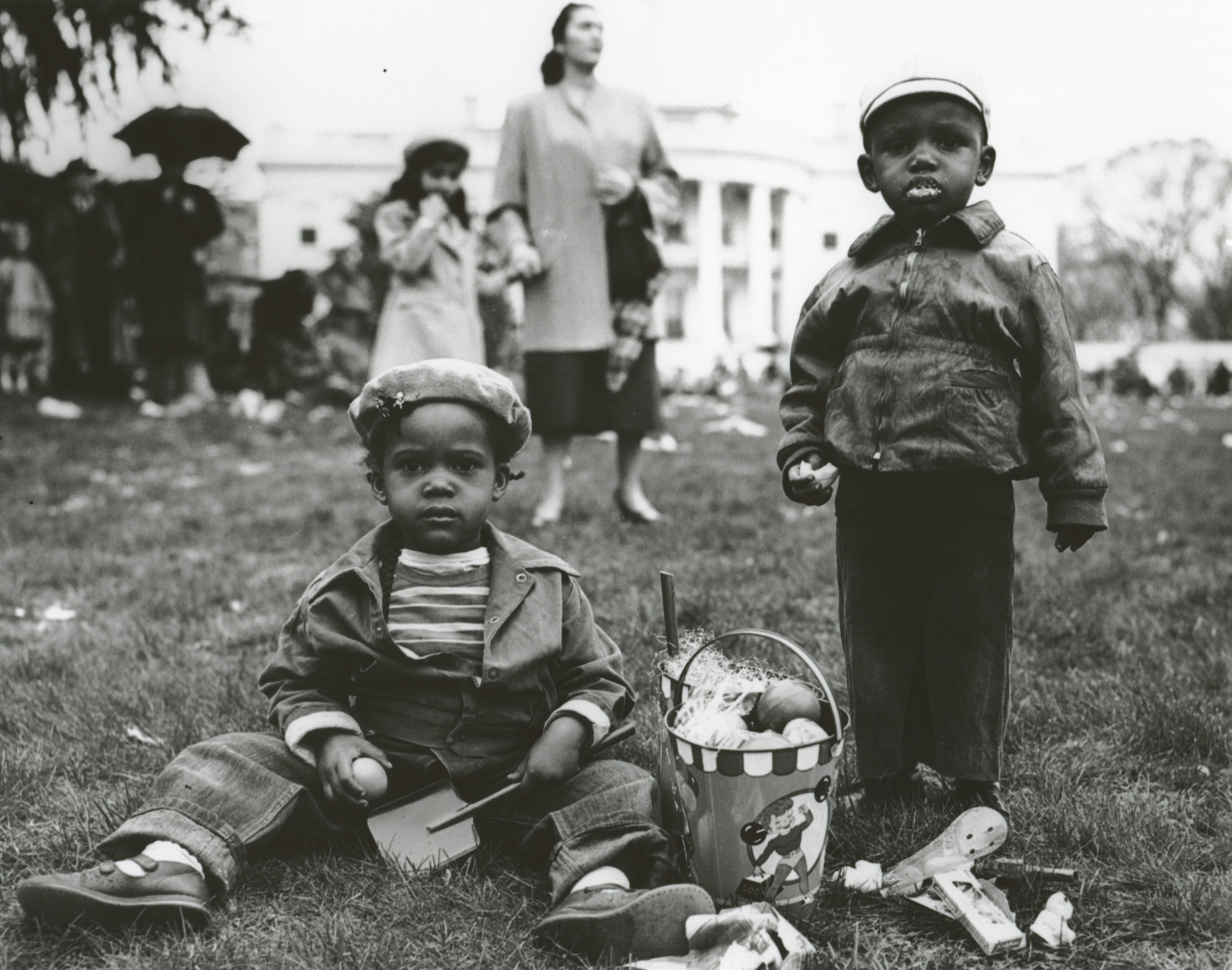 In this photograph taken by National Park Service Photographer Abbie Rowe on April 6, 1953, two young children enjoy treats from the their Easter basket at the annual White House Easter Egg Roll. (1953) (National Archives)