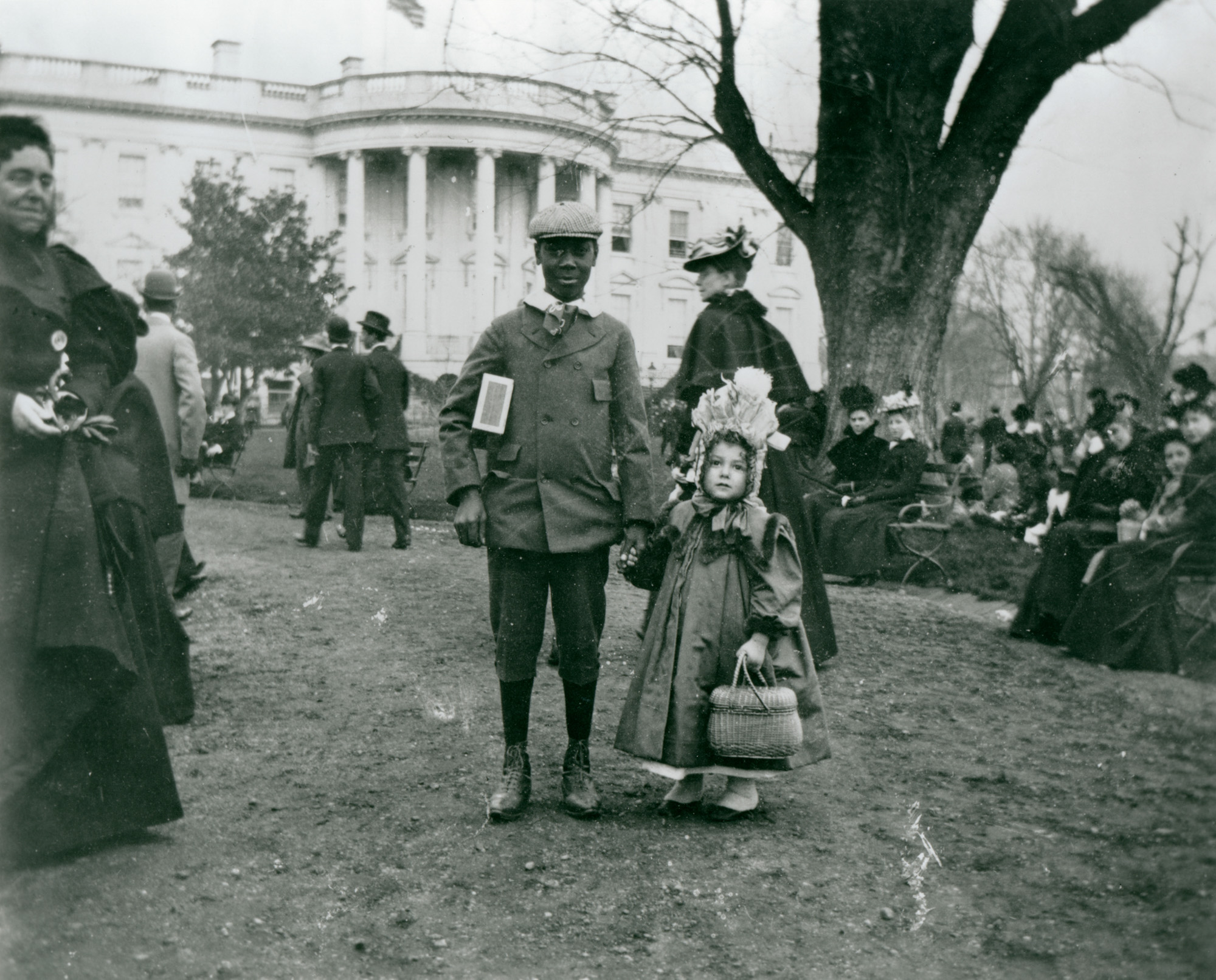 In this photograph taken by Francis Benjamin Johnston in 1898, a boy and a girl hold hands during the annual White House Easter Egg Roll. (1898) (Library of Congress)