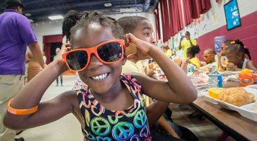 A smiling girl with orange glasses at lunch provided through assistance from the U.S. Department of Agriculture's (USDA) Food Nutrition Service (FNS). (Photo courtesy of the U.S. Department of Agriculture)