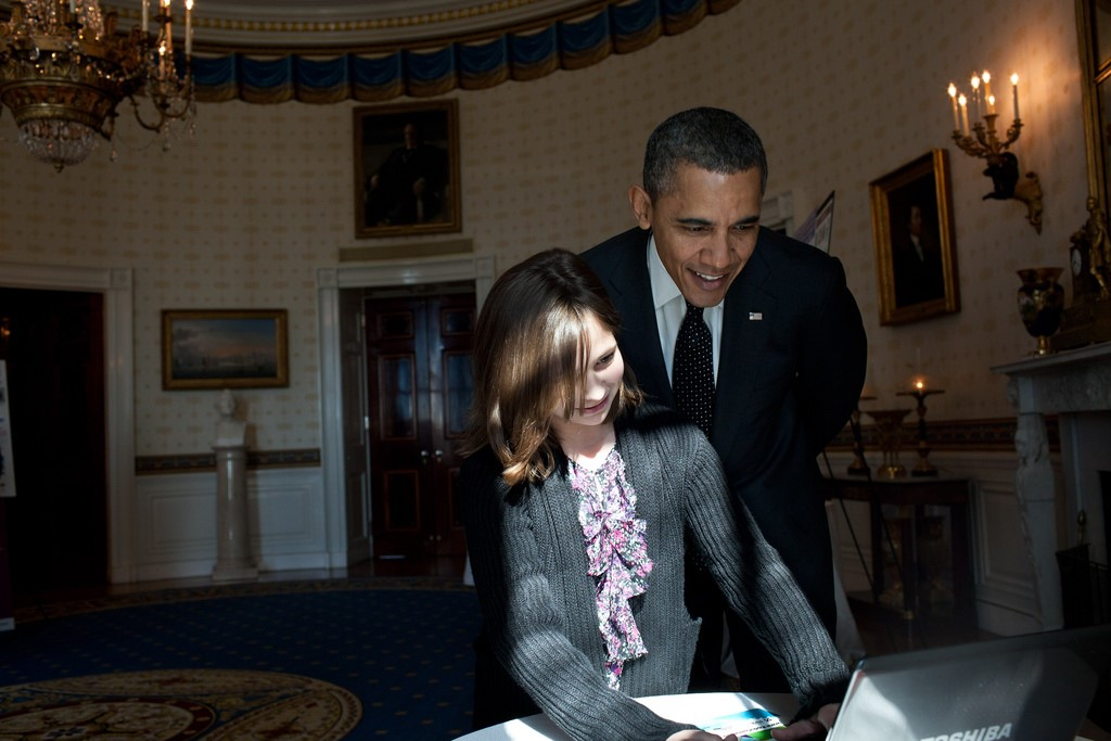President Obama looks over the shoulder of Hannah Wyman, 11, as she demonstrates her project -- designing and coding a videogame about the environment --  in the Blue Room, Feb. 7, 2012, during the second annual White House Science Fair celebrating student winners of science, technology, engineering, and math (STEM) competitions from across the country (Photo by Pete Souza)