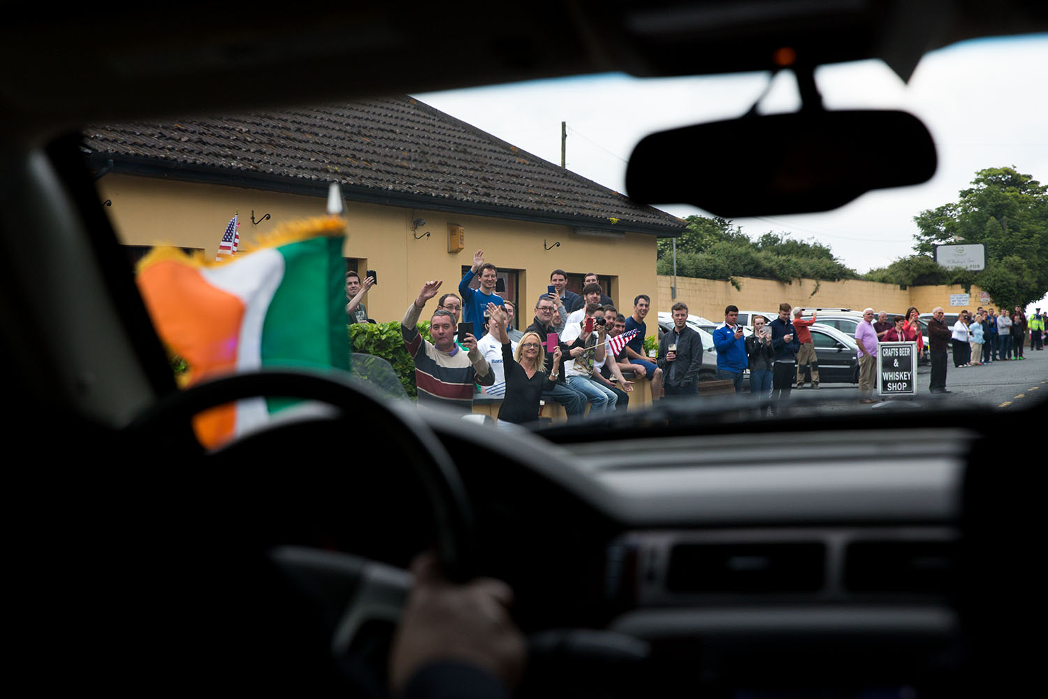 People waving american flags outside a pub along the motorcade route in County Louth, Ireland, June 25, 2016. (Official White House Photo by David Lienemann)