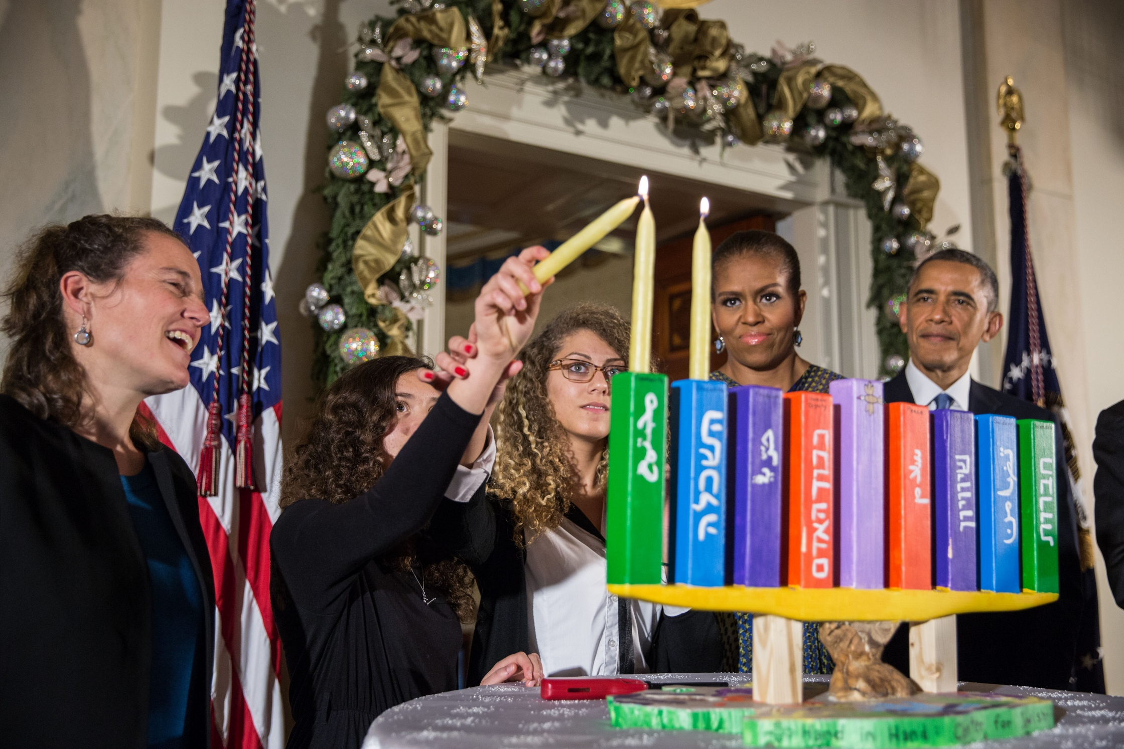 President Barack Obama, First Lady Michelle Obama, Rabbi Bradley Artson, and students from Hand in Hand participate in the Menorah lighting during the afternoon Hanukkah reception in the Grand Foyer of the White House, Dec. 17, 2014. (Official White House Photo by Pete Souza)