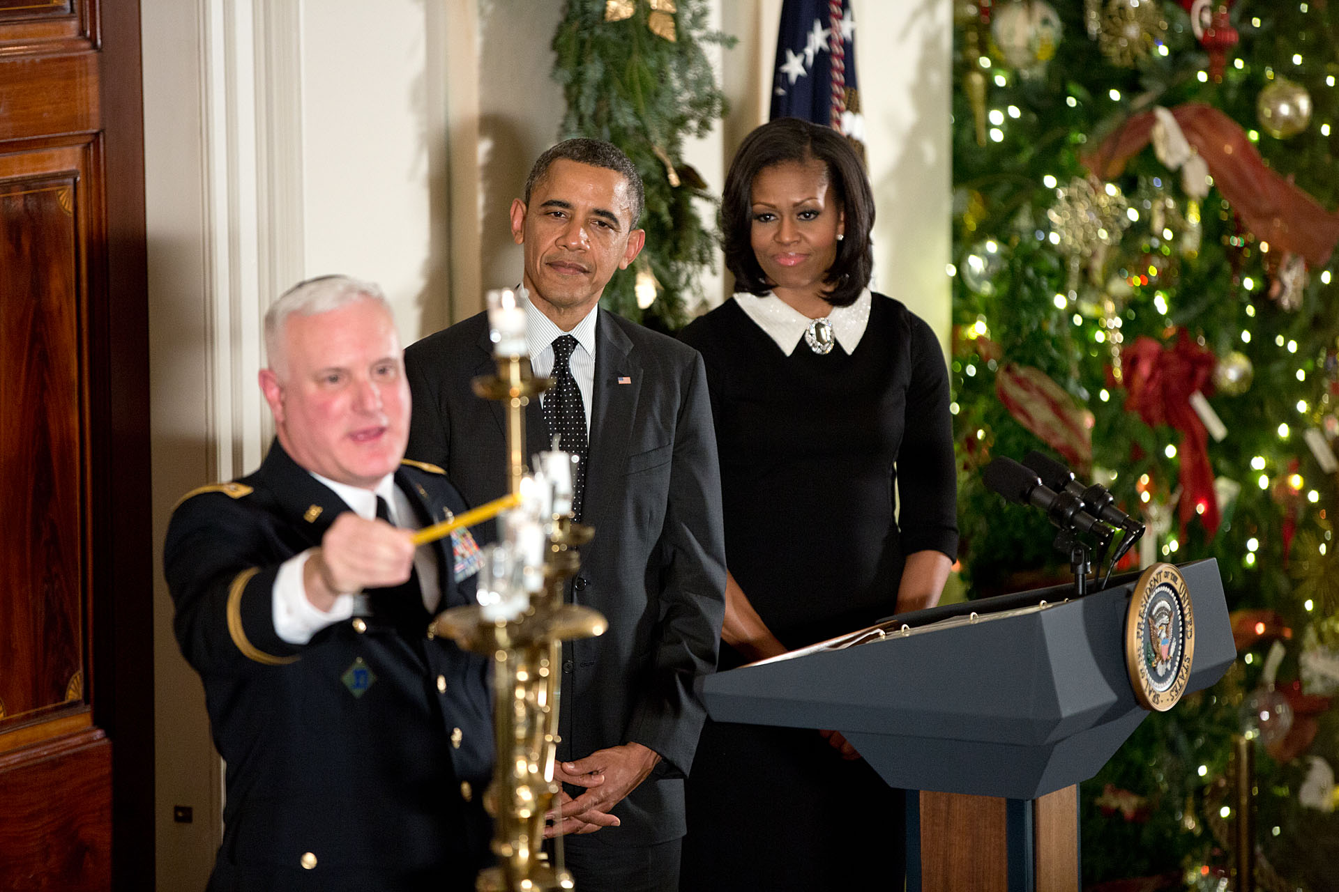 President Barack Obama, First Lady Michelle Obama, and Rabbi Larry Bazer participate in the Menorah lighting during the Hanukkah reception in the Grand Foyer of the White House, Dec. 13, 2012. (Official White House Photo by Pete Souza)