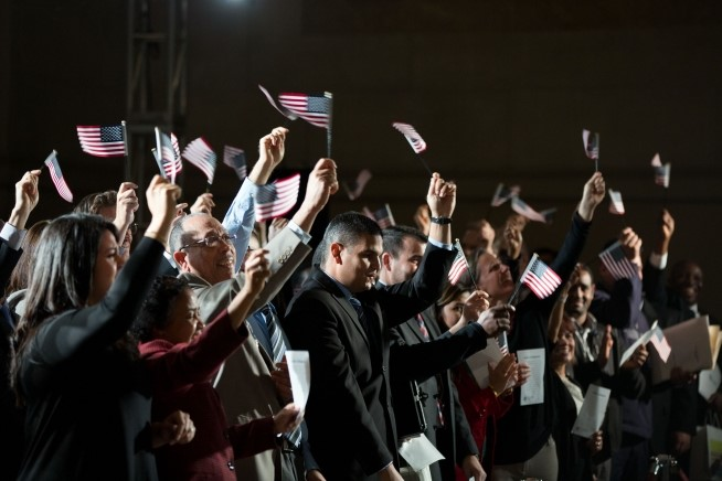 Newly naturalized citizens wave American flags after taking the Oath of Allegiance during a naturalization ceremony keynoted by the President at the National Archives in Washington, D.C., Dec. 15, 2015. (Official White House Photo by Pete Souza)