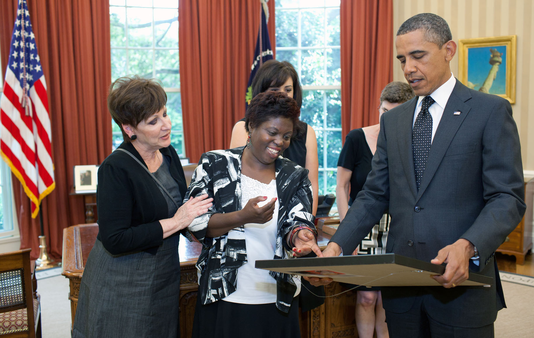 President Barack Obama looks at a painting presented to him by artist Lois Curtis, center, during their meeting in the Oval Office, June 20, 2011. Joining them are, from left, Janet Hill and Jessica Long, from the Georgia Department of Labor, and Lee Sanders, of Briggs and Associates. (Official White House Photo by Pete Souza)