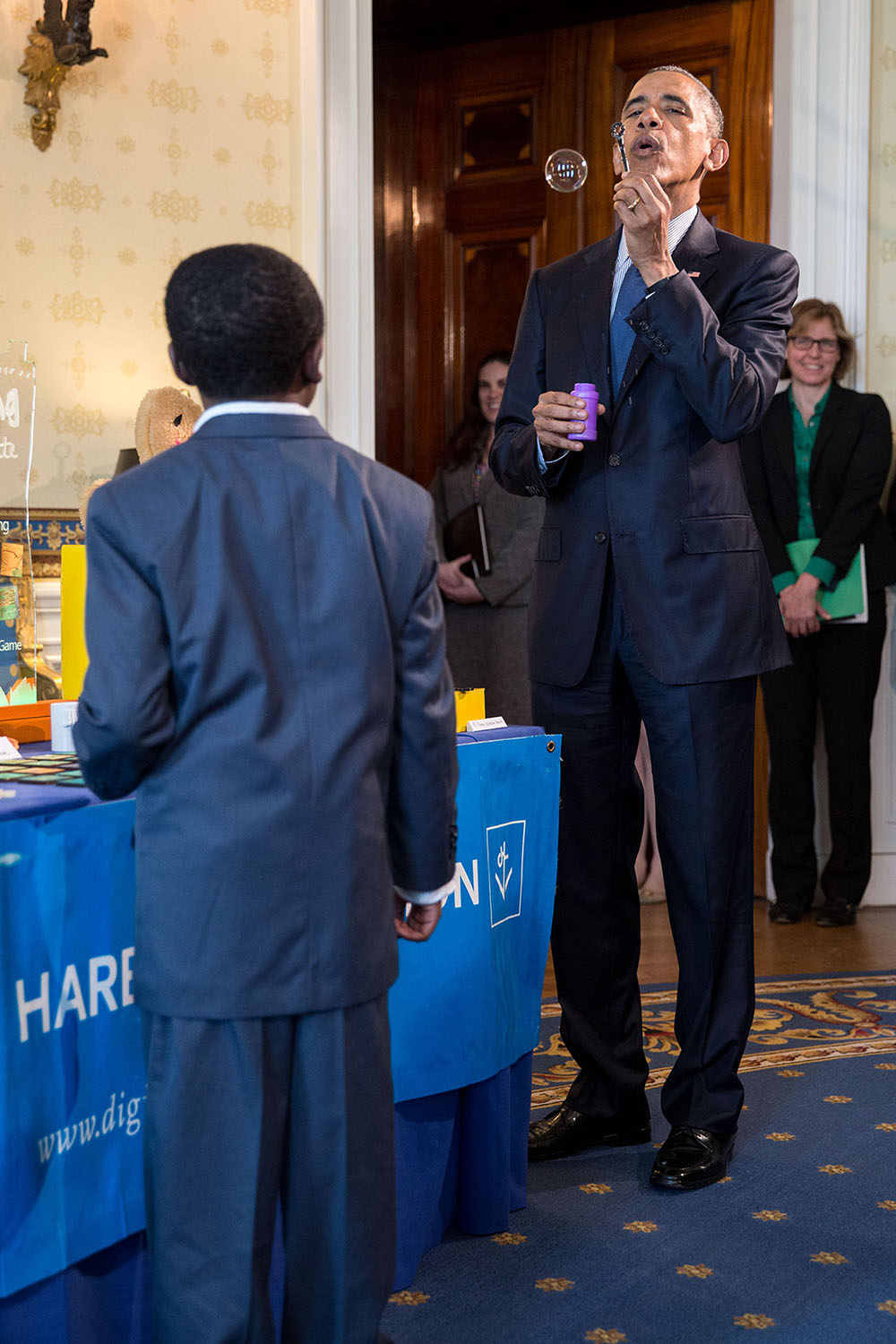 President Barack Obama blows a bubble while talking with nine-year-old Jacob Leggette about his experiments with additive and subtractive manufacturing with a 3D printer, his project that was part of the White House Science Fair in the Blue Room of the White House, April 13, 2016. (Official White House Photo by Pete Souza)