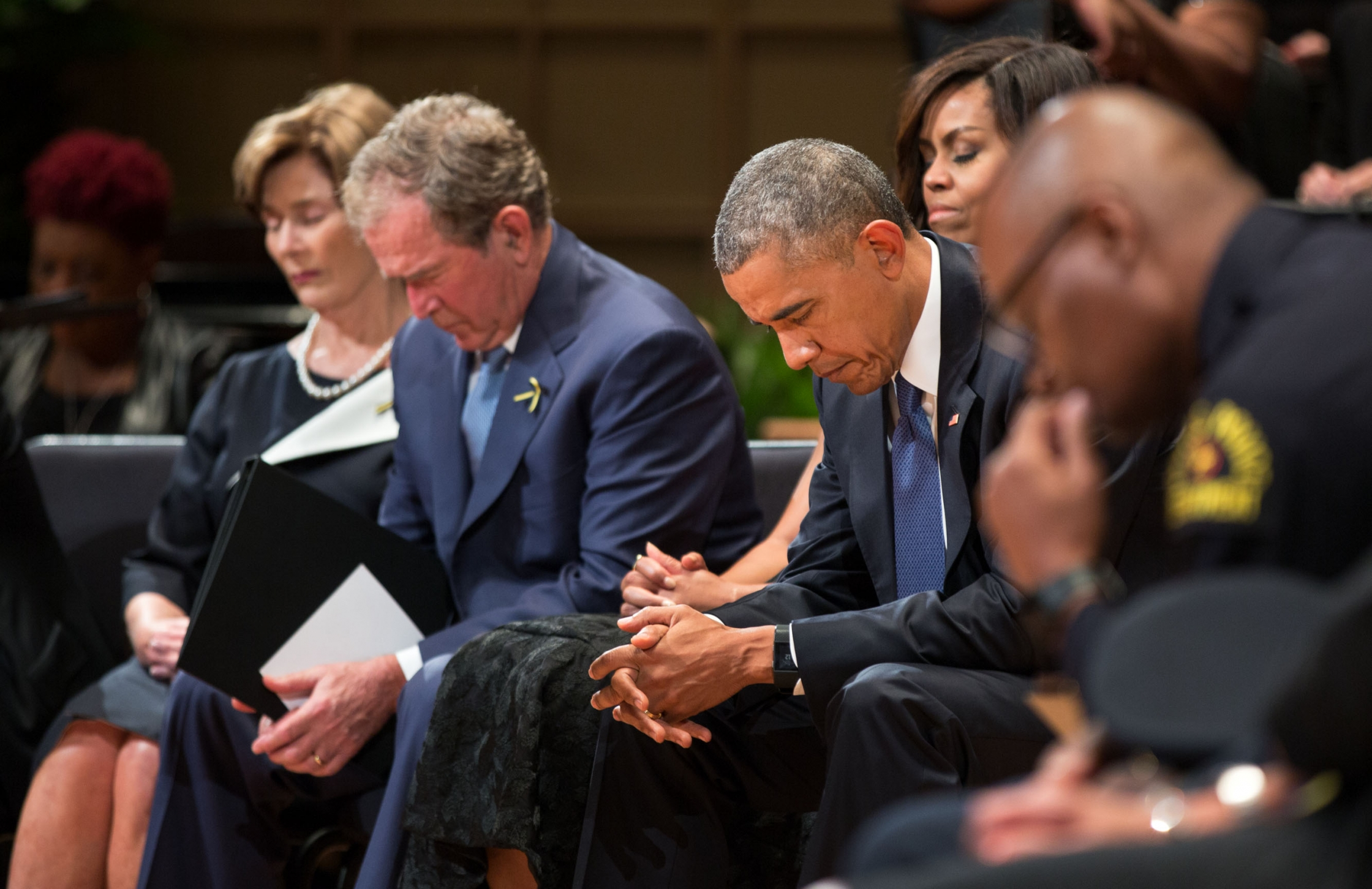 President Barack Obama, First Lady Michelle Obama, former President George W. Bush and former First Lady Laura Bush bow their heads during a prayer at the Interfaith Memorial Service for five fallen police officers in Dallas, Texas, July 12, 2016. Dallas Police Chief David Brown is at right. (Official White House Photo by Pete Souza)
